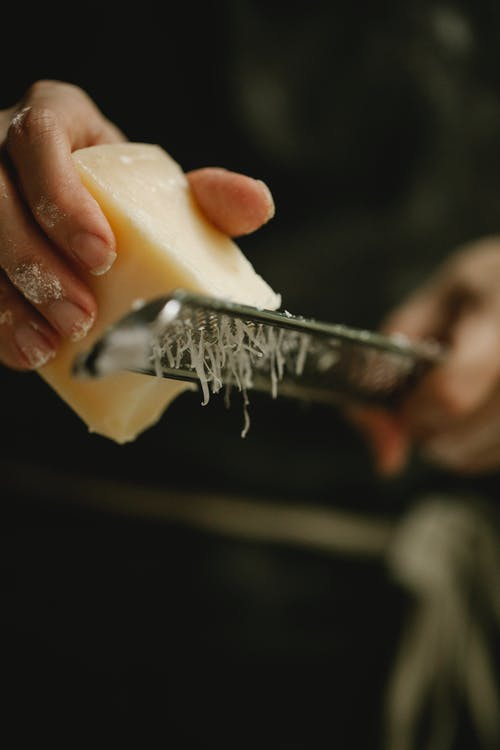 Crop unrecognizable female chef grating hard cheese on grater while cooking in kitchen