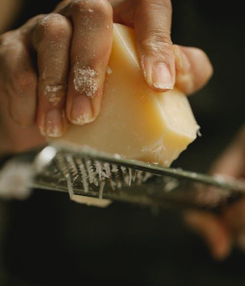 Crop unrecognizable chef grating delicious cheese