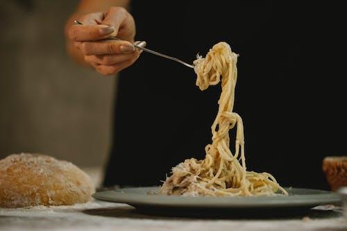 Crop unrecognizable woman eating spaghetti in cream sauce
