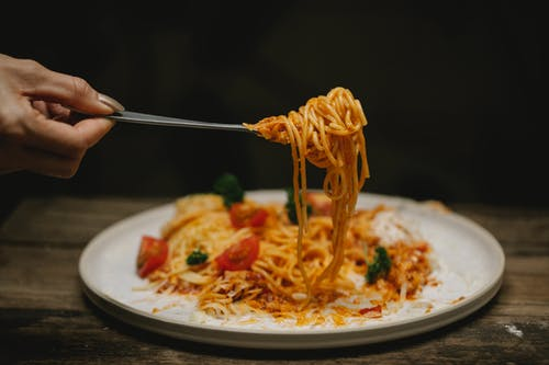 Crop anonymous female with fork enjoying yummy Bolognese pasta garnished with cherry tomatoes and parsley
