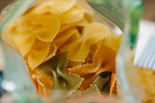 Pack of dry raw farfalle pasta placed on table