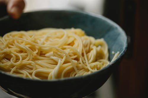 Anonymous person demonstrating bowl with delicious spaghetti