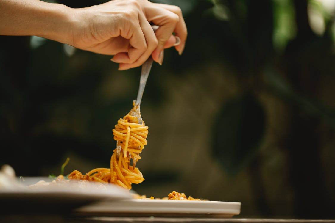 Crop anonymous female rolling delicious spaghetti with tomato sauce on fork during dinner in restaurant