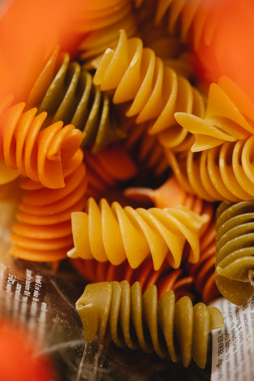 Raw colorful rotini pasta in container