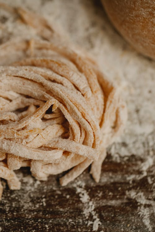 Dough of homemade fresh thin pasta placed on wooden table covered with flour