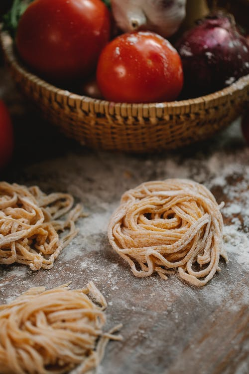 Dough of fresh noodle placed on table near vegetables