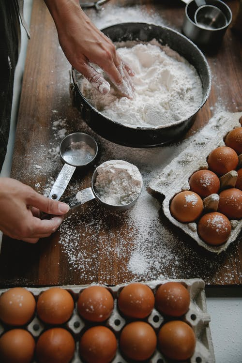 Woman cooking dough on table with eggs and flour