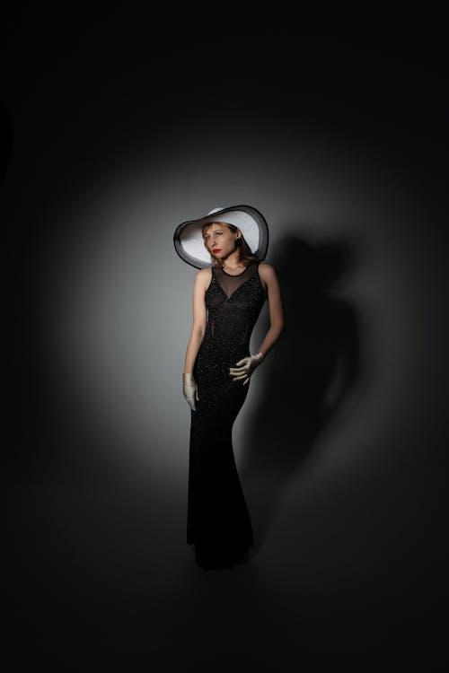 Mulher De Vestido Preto Sem Mangas Com Fones De Ouvido Brancos