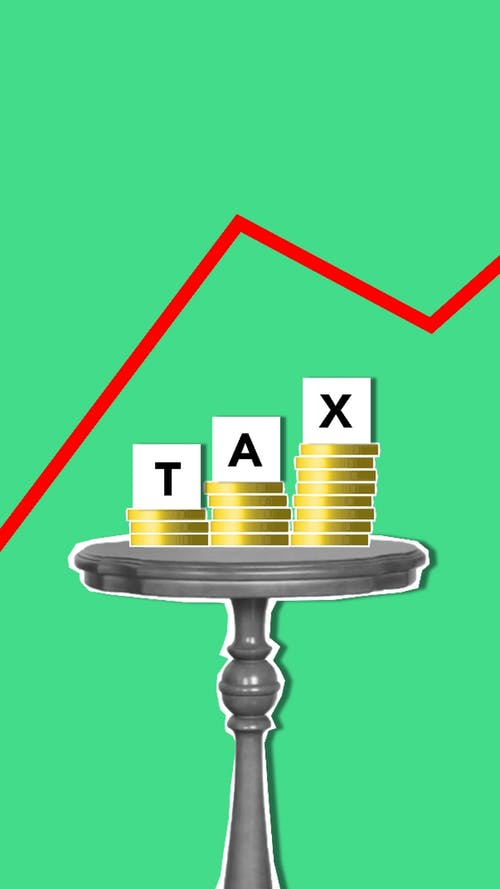 Cutout paper composition representing concept of tax with coins on table under graph on green background