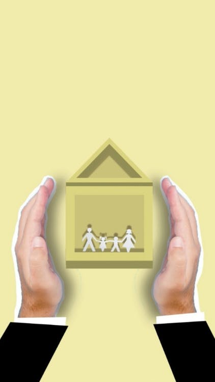 Creative image of cutout faceless person showing vector house image with family members inside