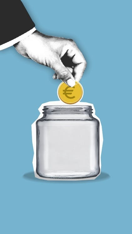 Crop faceless person putting coin into glass jar