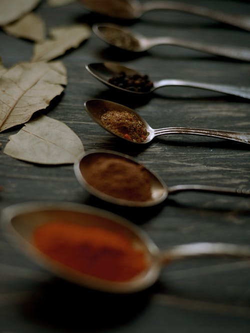 Lined Up Spoons Full of Assorted Spices