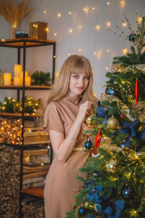 Positive female in dress looking at camera while hanging bauble on decorated coniferous tree in room with glowing garlands and shelves