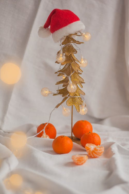 Small plastic Christmas tree with lanterns and tangerines