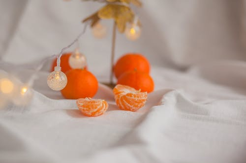 New Year composition of bright fresh mandarins and glowing garland with lanterns on white background