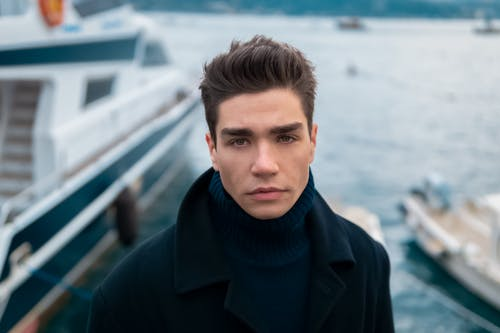 Man in Black Coat and Blue Scarf