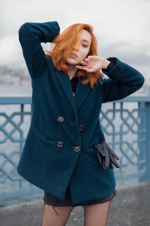 Woman in Black Coat Standing Near Blue Metal Fence