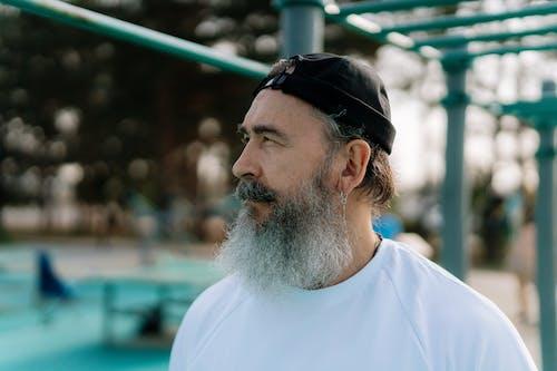 Bearded Man Wearing a Cap in a Park