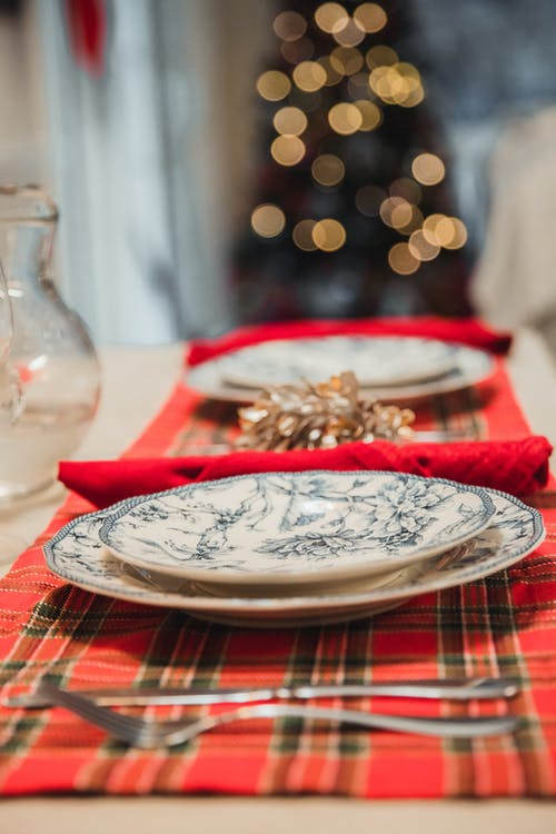 Table with silverware and porcelain plates placed on checkered red napkins near jug with  blurred garland on Christmas tree on background