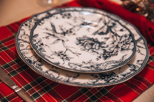 From above of porcelain plate with ornamental elements served on checkered cloth with silverware on table during holiday celebration in room with blurred background