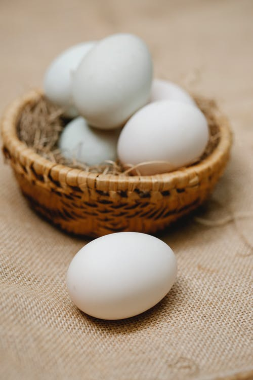 White chicken eggs placed in wicker bowl on table