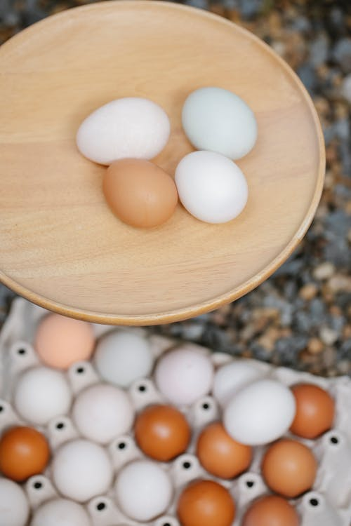 From above of brown and white chicken eggs placed on round shaped timber board and carton box