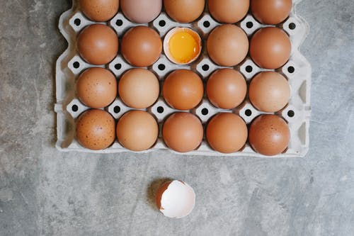 Top view of chicken eggs in rows in paper container placed on table for cooking