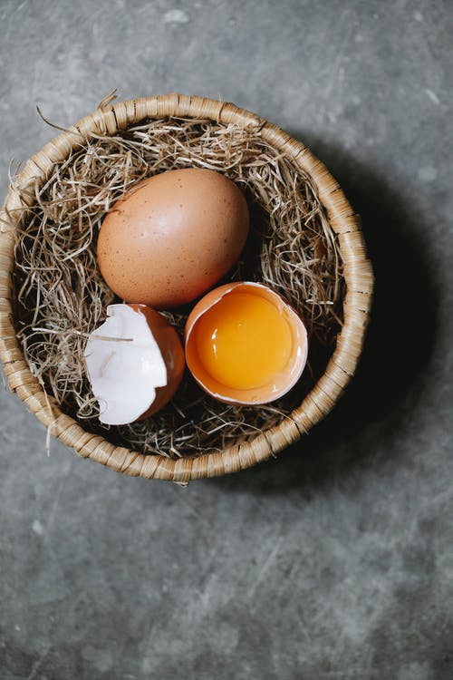 Cracked eggs on hay in wicker bowl