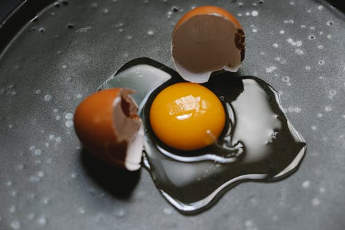 Cracked egg on pan for cooking breakfast