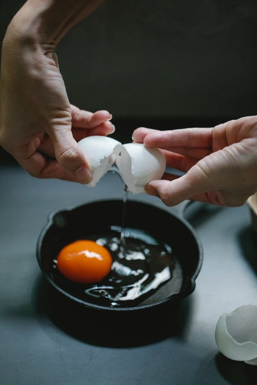 Woman breaking eggs into pan for breakfast