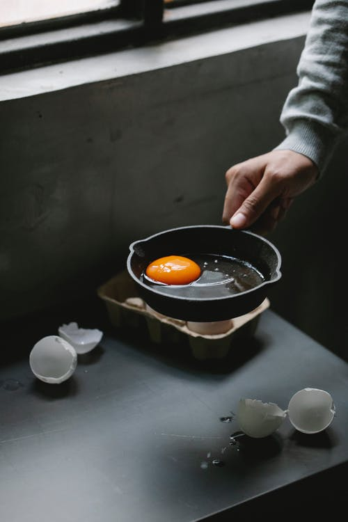 Person with pan of uncooked eggs