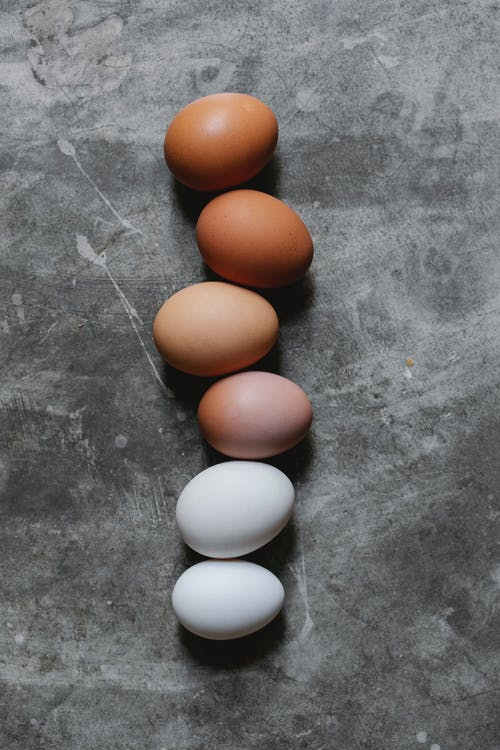 Top view of raw white and brown chicken eggs arranged in row on gray table in kitchen during Easter preparation