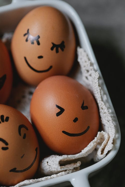 From above of brown chicken eggs with different painted funny faces placed in ceramic dish in kitchen