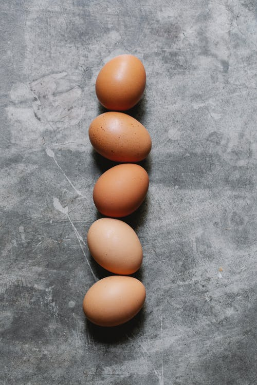 Top view of fresh healthy raw brown eggs placed in row on gray surface in kitchen