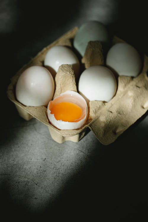 High angle of rustic carton container with uncooked fresh white whole and broken chicken eggs placed on table in sunlight