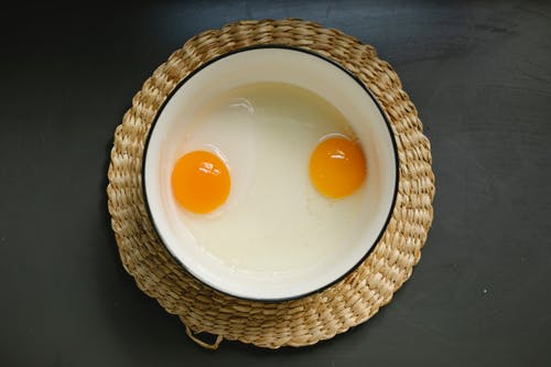 Top view of enamel bowl with fresh uncooked eggs yolks and whites placed on wicker rattan charger plate before breakfast preparation