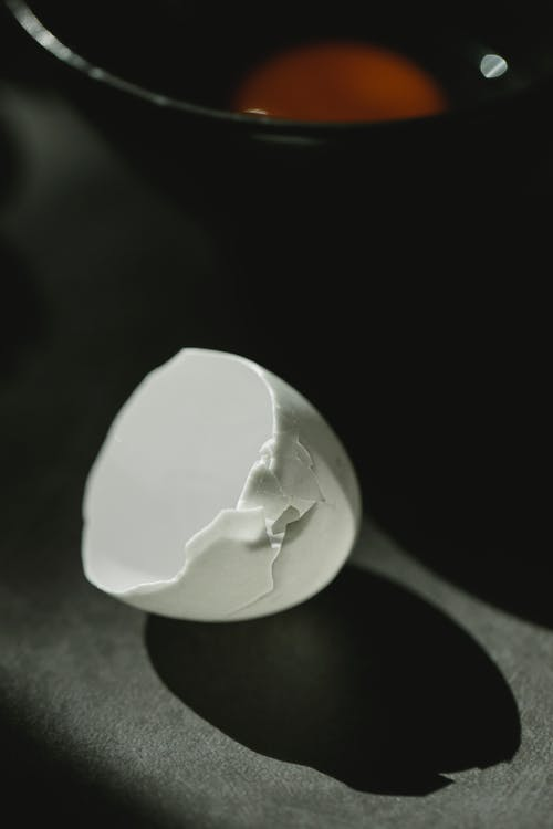 From above of fragile white broken eggshell scattered on table near bowl with yolk in kitchen