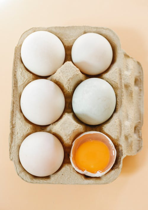 Box of healthy organic chicken eggs on beige surface