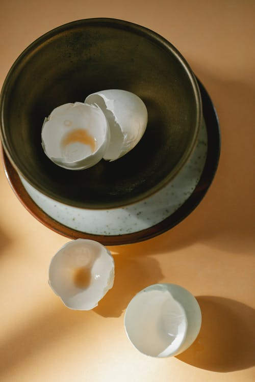 Eggshells in bowl and on table in kitchen