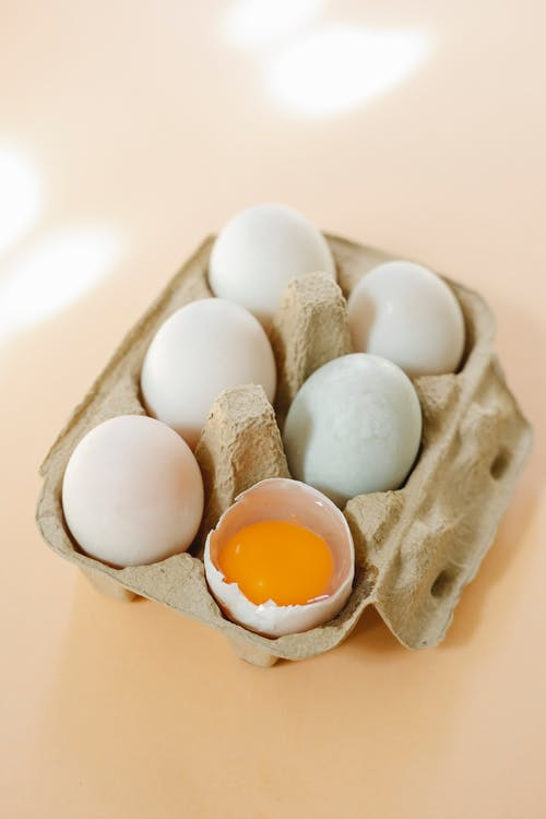 High angle of broken white chicken egg with vibrant yolk placed in filled carton box on beige surface in kitchen in sunny morning