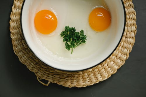Bowl with uncooked egg yolks and whites with herbs in kitchen