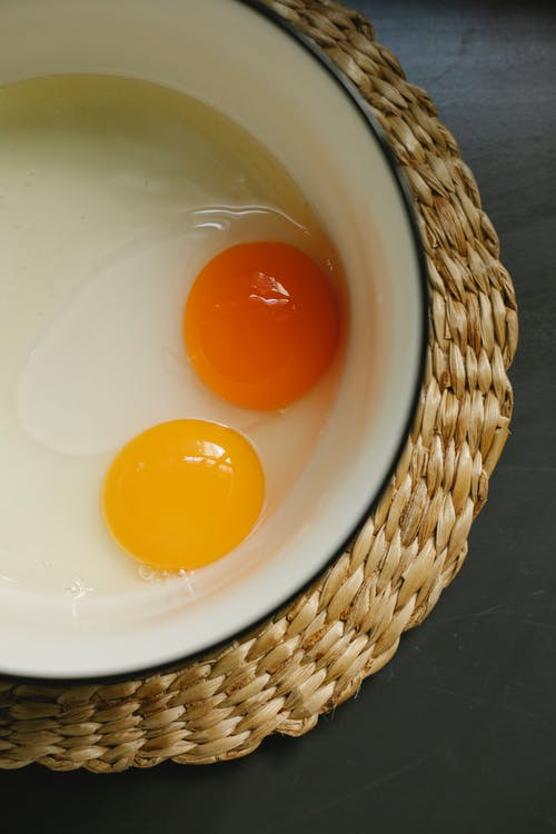 Raw eggs in enamel bowl placed on rattan placemat in morning