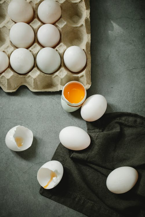Top view composition of raw organic eggs placed in egg carton and scattered on dark table in kitchen