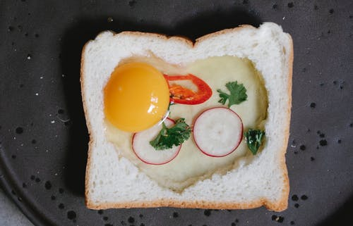 Top view yummy raw egg toast with white bread reddish and chili pepper placed on pan