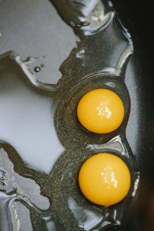 Eggs frying in black pan