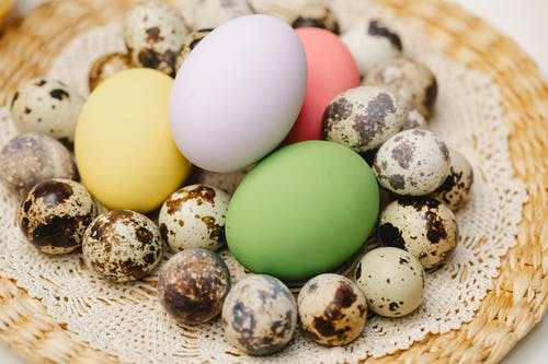 From above of multicolored eggs and heap small spotted quail eggs placed on lace doily during Easter holiday in kitchen