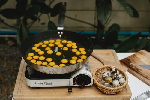 From above abundance of small quail eggs frying in pan on cooker on wooden board with heap of eggs in kitchen
