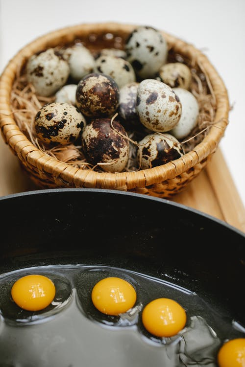 From above of many small eggs frying in black pan on wooden surface near wicker bowl with heap of quail eggs