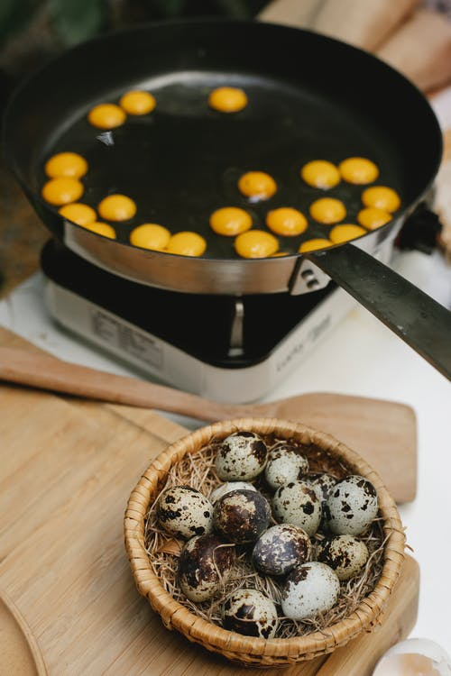 From above of many small quail eggs frying in pan on cooker near heap of eggs on wooden cutting board in kitchen