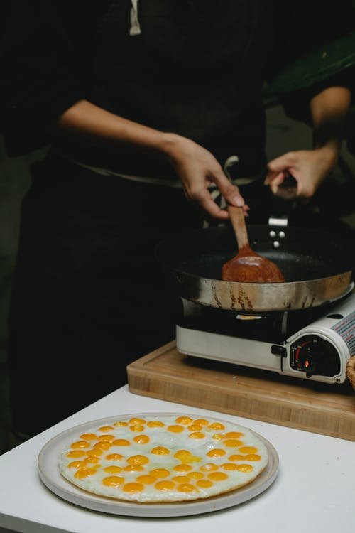 Crop anonymous cook placing wooden spatula in pan placed on stove near freshly fried quail eggs on plate
